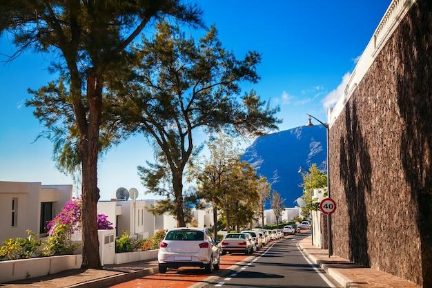 Petite rue confortable avec des voitures en stationnement dans le quartier résidentiel de los gigantes, tenerife, canaries, espagne