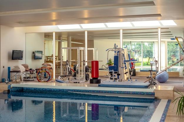 Petite salle de sport avec appareils de musculation et appareils de fitness dans la piscine intérieure de la maison
