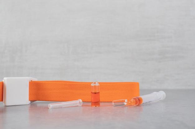 Petite seringue avec un liquide marron sur une surface grise