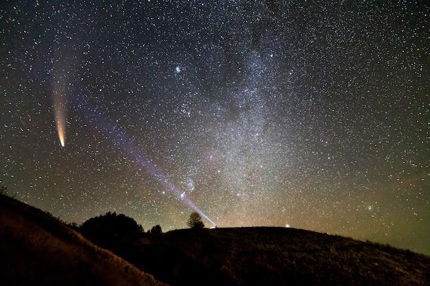 Petite silhouette d'un scientifique avec une lampe de poche sur la tête pointant un faisceau de lumière brillant sur le ciel