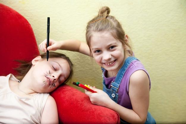 Petite sœur dessine des visages sur le visage de sa sœur aînée avec un stylo-feutre