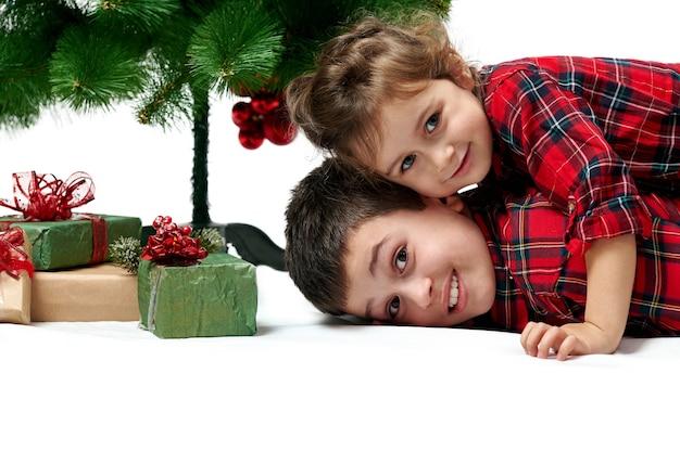 La petite sœur est allongée sur son frère à côté des boîtes avec des cadeaux