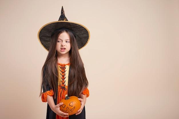Petite sorcière avec citrouille d'halloween