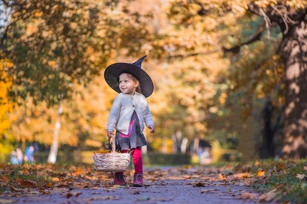 Petite sorcière fille marche dans la forêt d'automne avec un panier de feuilles.