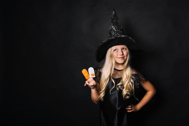 Petite sorcière gesticulant la victoire et regardant ailleurs