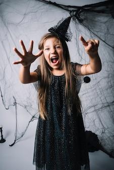 Petite sorcière tenant une araignée et rugissant