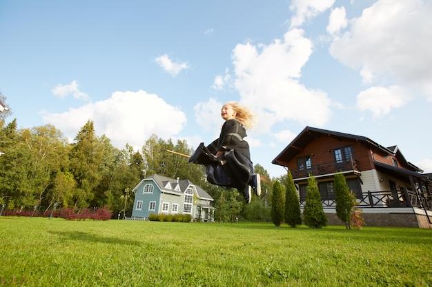 Petite sorcière volant sur manche à balai