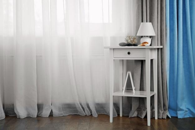 Petite table blanche avec lampe sur fond de rideau