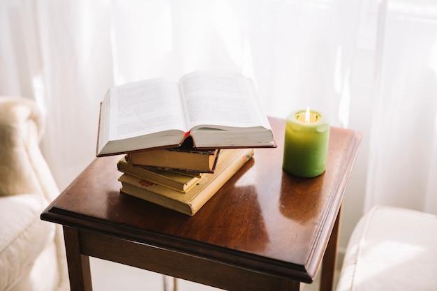 Petite table avec des livres et une bougie