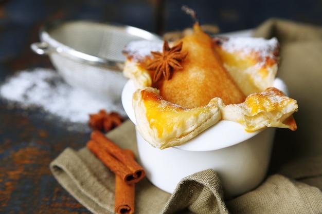Petite tarte aux poires en tasse, sur table en bois