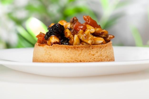 Petite tartelette ronde aux garnitures variées, tartelette croustillante aux noisettes, cacahuètes et autres ingrédients, tartelette pâte aux noix et fruits secs recouverte de caramel