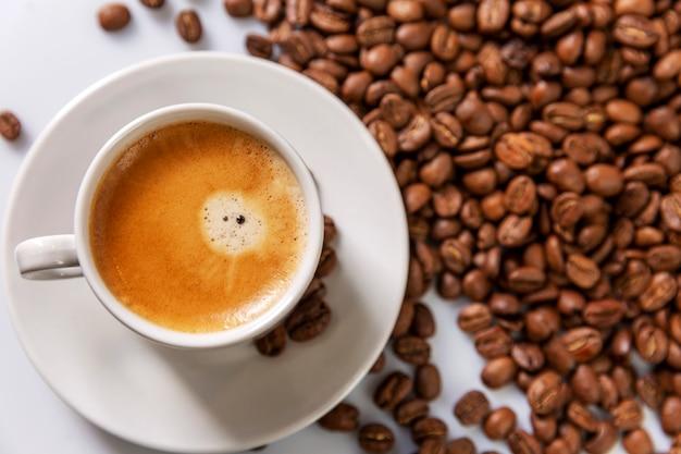 Une petite tasse de café blanc se dresse sur des grains de café. plaisir parfumé.