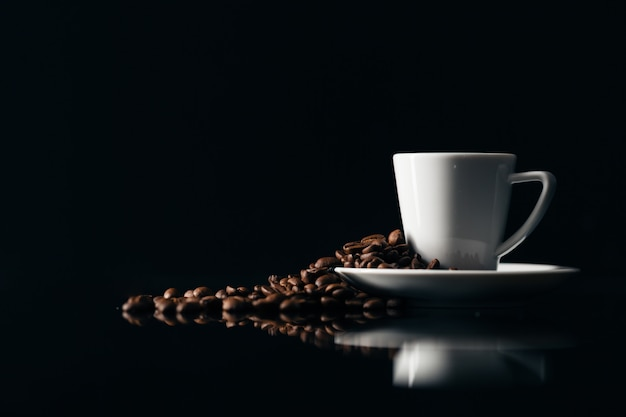 Petite tasse de café noir sur fond sombre avec des grains de café