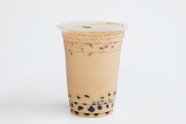 Petite tasse en plastique thé au lait glacé style taiwan sur fond blanc, boisson sucrée fraîche et fraîche, concept de boisson sucrée fraîche isolée, nourriture et boisson