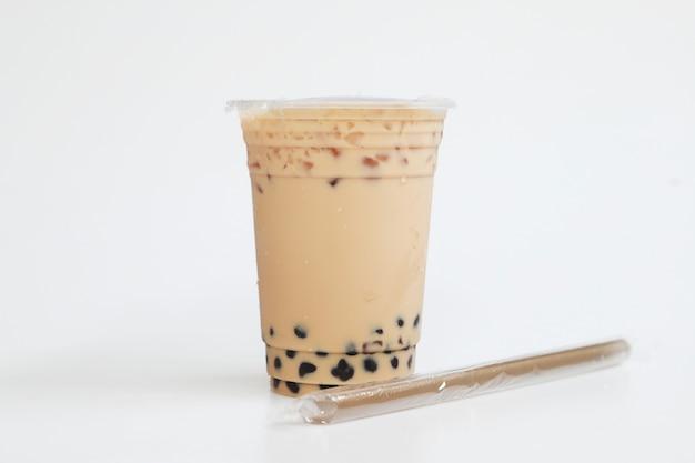 Petite tasse de thé au lait glacé style taiwan avec de la paille sur fond blanc, concept de boisson sucrée fraîche et fraîche, nourriture et boisson