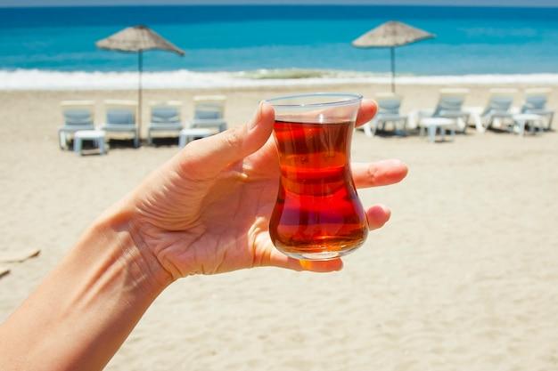 Petite tasse en verre avec du thé sur le fond de la mer bleue, des parasols de plage et de plage.