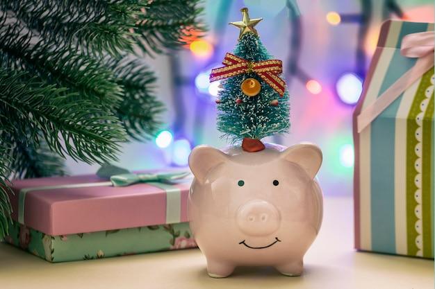 Une petite tirelire avec un arbre sur la tête. en arrière plan, cadeaux et guirlandes en flou.
