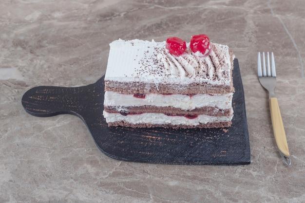 Petite tranche de gâteau avec garniture de crème, cerise et poudre de cacao sur une planche en marbre