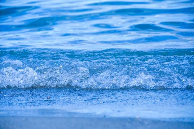 La petite vague bleue de mer se lave jusqu'au rivage. espace de copie
