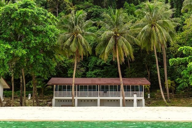 Une petite villa sur l'île et le décor d'une petite forêt.