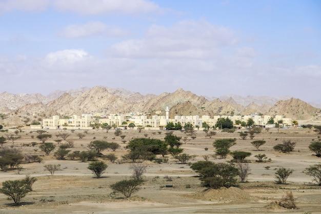 Petite ville moderne des emirats arabes unis dans le désert au pied des montagnes