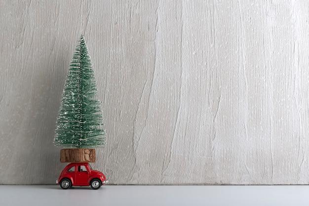 Petite voiture avec arbre de noël sur le toit. voiture en cadeau sous le sapin. espace de copie.