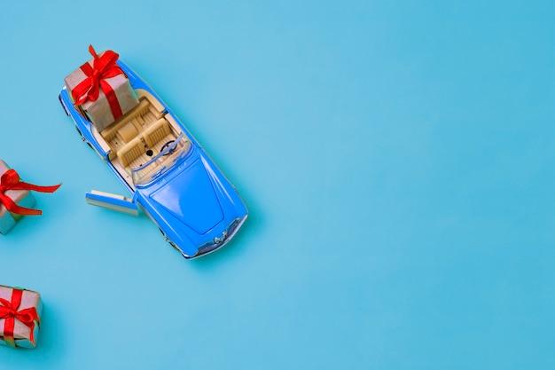 Petite voiture bleue avec cabriolet à toit ouvert portant un cadeau avec un arc rouge sur fond bleu