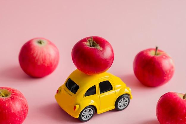 Petite voiture boule jaune avec des pommes rouges sur un rose pastel