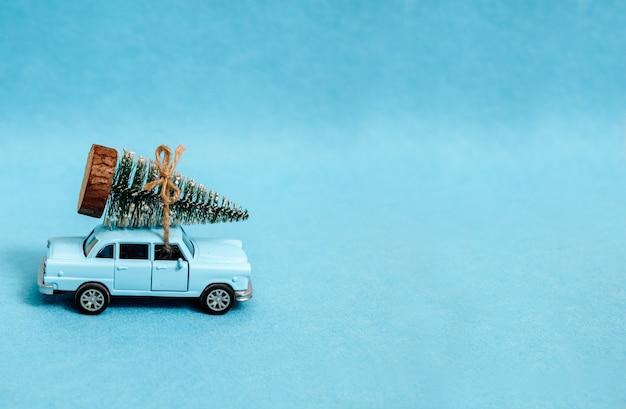 Une petite voiture conduit un arbre de noël. sur fond bleu.