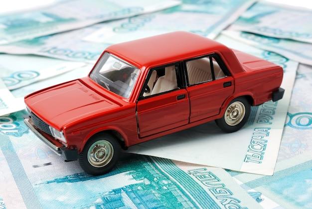 Petite voiture sur le fond des billets de banque.