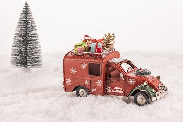 Petite voiture jouet décorée d'ornements sur la neige artificielle avec un arbre de noël en arrière-plan