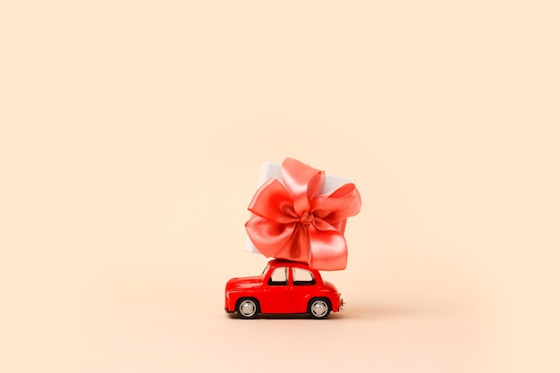 Petite voiture jouet rétro rouge avec cadeau sur le toit rose