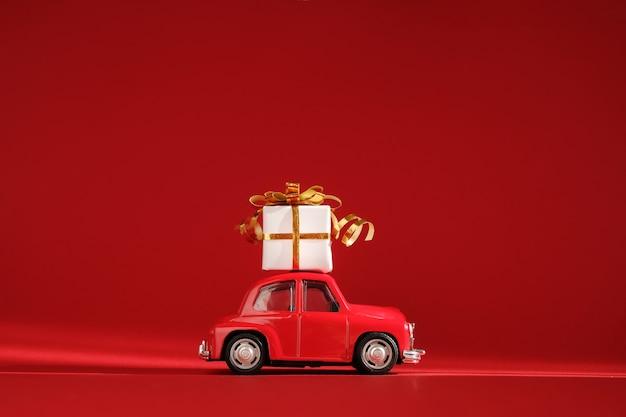 Petite voiture de jouet rétro rouge avec cadeau sur le toit.
