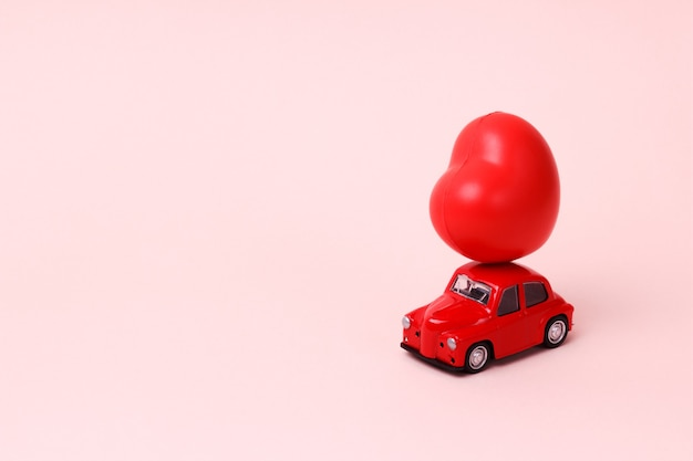 Petite voiture jouet rétro rouge avec coeur sur le toit sur le concept de livraison présent rose saint valentin