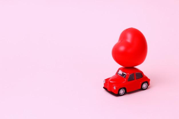 Petite voiture jouet rétro rouge avec coeur sur le toit rose