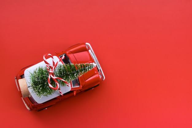 Petite voiture jouet rouge et arbre de noël sur le rouge. vue de dessus