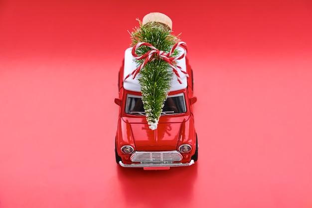 Petite voiture jouet rouge et arbre de noël sur le rouge.