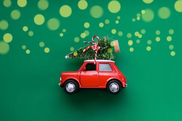 Petite voiture jouet rouge et arbre de noël sur vert. vue de dessus