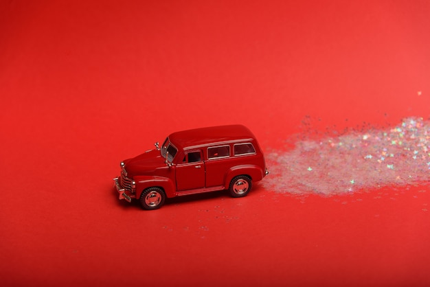 Une petite voiture laisse une traînée rougeoyante de confettis