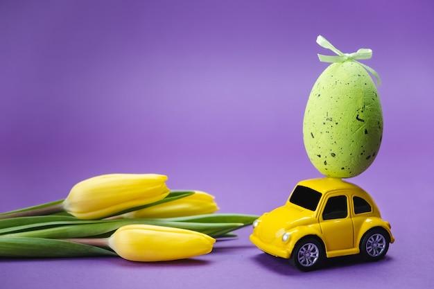 Petite voiture avec un œuf de pâques sur le toit