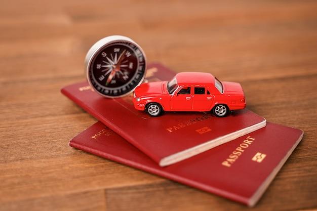 Une petite voiture sur les passeports étrangers et une boussole. composition touristique sur une table en bois