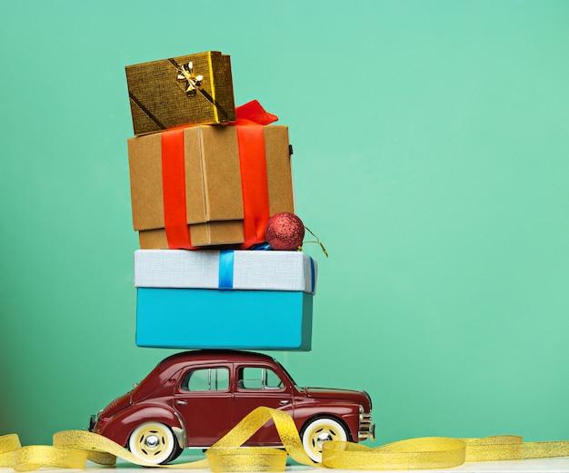 Petite voiture rétro bleue offrant des cadeaux de noël ou du nouvel an, sur jaune