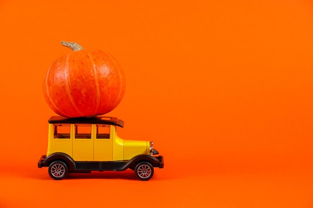 Petite voiture rétro avec une citrouille sur fond orange concept de récolte d'halloween et d'automne