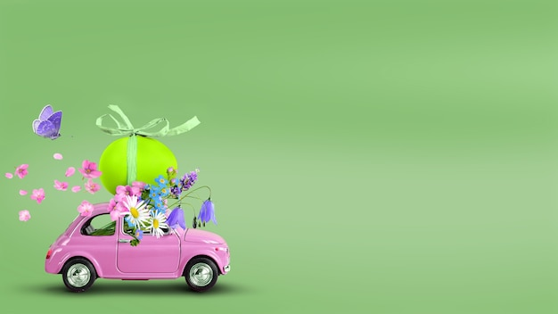 Petite voiture rétro rose transportant un œuf de pâques et un bouquet de fleurs sur fond vert. espace de copie