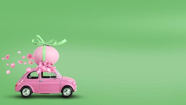 Petite voiture rétro rose transportant un œuf de pâques sur le toit sur fond vert. espace de copie