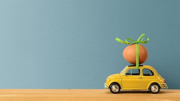 Petite voiture rétro transportant un œuf de pâques sur le toit. notion de pâques. espace de copie