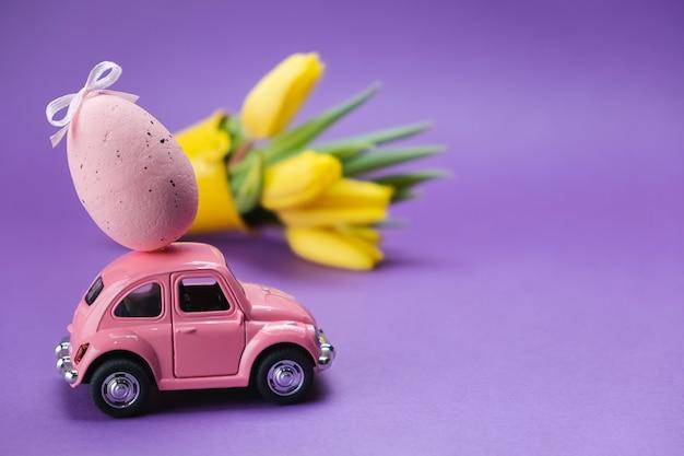 Une petite voiture rose porte un œuf rose sur une surface violette
