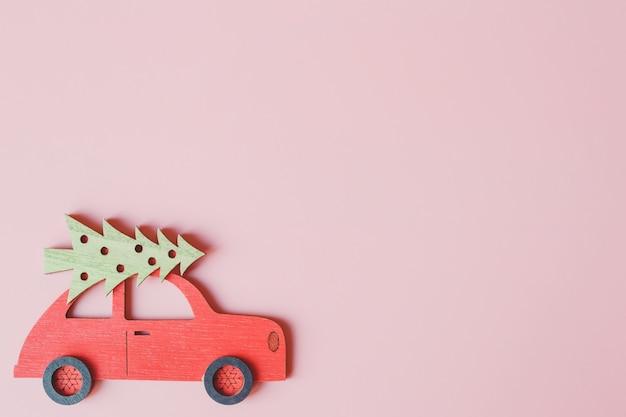 Petite voiture rouge avec arbre de noël, sur fond rose