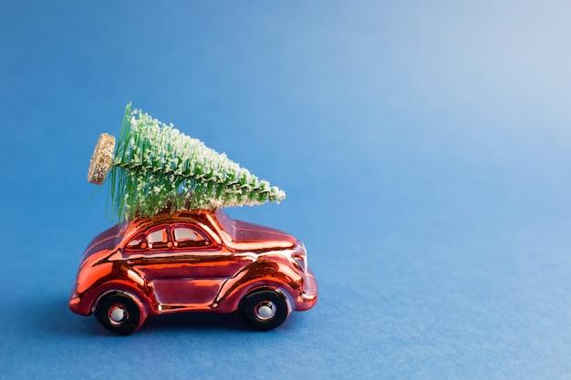 Petite voiture rouge avec un arbre de noël sur le toit, fond bleu tendance. couleur de l'année