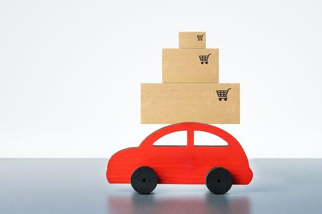 Petite voiture rouge avec des boîtes sur fond gris. livraison à domicile.